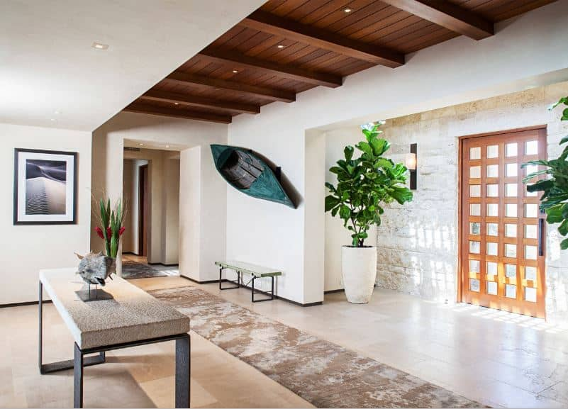 This foyer has a beautiful wooden main door filled with small glass panels that bring in natural lights to the white walls that are accented with large potted plants. a painting and even a small canoe mounted above the small bench for the waiting guests.