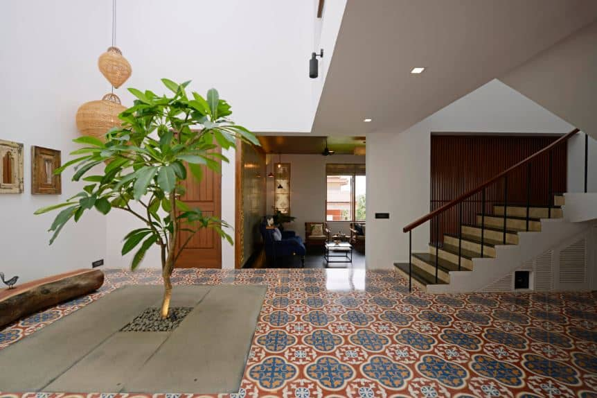This amazing Tropical-style foyer has a tropical tree planted right in the middle. It has a small yellow spotlight to better emphasize against its gray floor that stands out against the rest of the floor that has colorful and bright patterns.