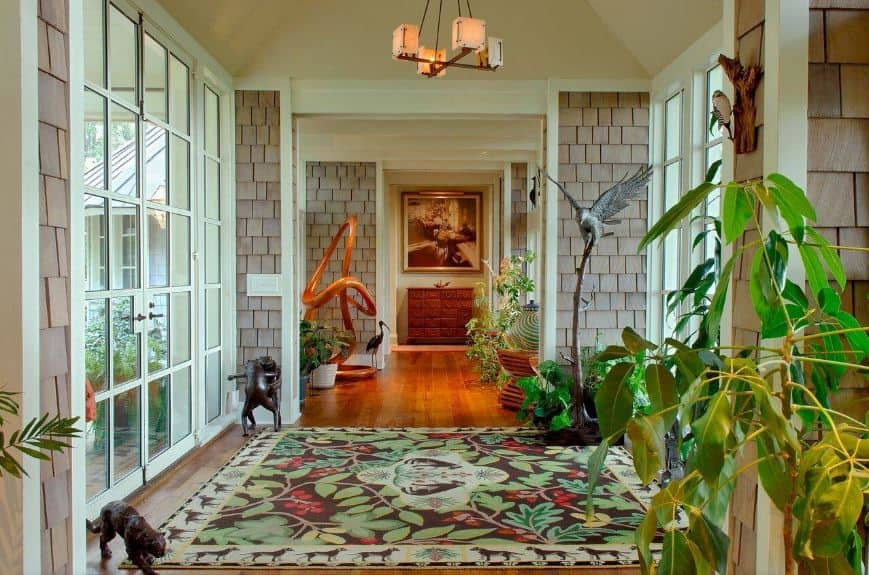 This eclectic foyer feels like you have stepped into a tropical forest upon entry of the glass doors. The hardwood flooring is mostly covered with an area rug that has leaves and flowers on it. This is surrounded by small dark wooden figurines of animals and also potted plants.