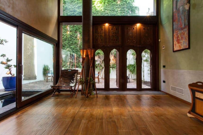 This Tropical-style foyer has a unique wooden main entrance that looks like entry doors to a temple. This is balanced with a massive transom glass window and glass walls to its side that is adorned with a couple of jungle torches and an animal hide hammock chair.