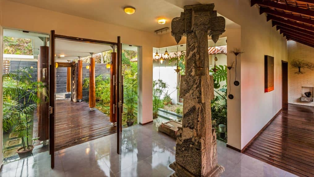 After you pass through the wooden walkway that is surrounded by ferns and ponds, you enter through the wooden double doors and come face to face with a stone column with distinct designs that caps off the Tropical-style aesthetic of this foyer with a slight hint of Aztec sensibility.
