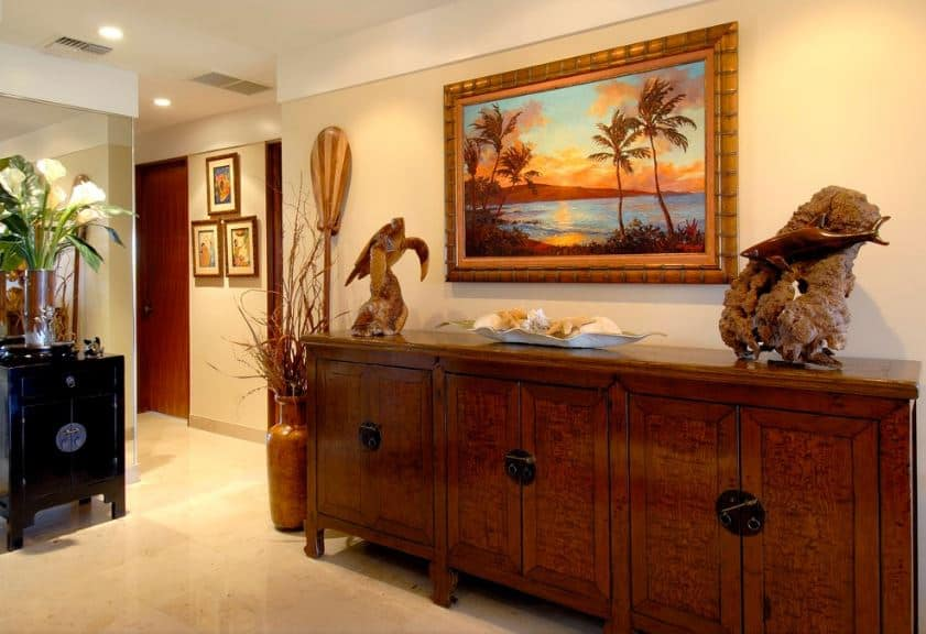 After entering the main door of this foyer, you are welcomed by the gorgeous wooden sculptures of sea animals on the large wooden console table with built-in cabinets topped with a beautiful painting of a tropical sunset complementing the beige wall.