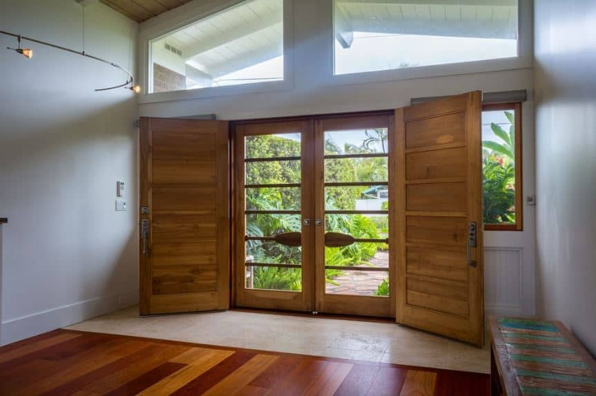 An abundance of natural lights cascade into this foyer through the large transom windows and the glass panels of the main doors that have wooden frames matching the wooden bench on the side. A couple of these frames look like oars that give the doors character.
