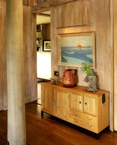 This Tropical-style foyer is dominated by its wooden elements on the hardwood flooring, walls, log columns and the small cabinet on the side that acts as console table. This is adorned with a couple of wooden sculptures and a photo of the sea to solidify its aesthetic.