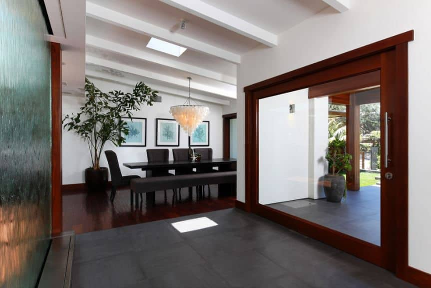 The large swivel door of this Tropical style foyer is mostly made of a single glass panel framed with redwood that stands out against the white walls and ceiling that has exposed wooden beams. Across from this door is a decorative glass panel that is frosted with running water.