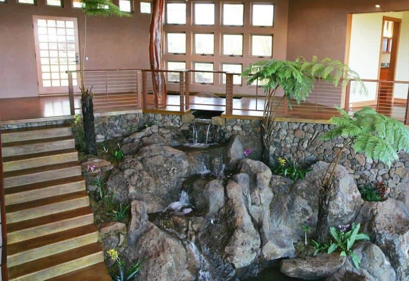 The highlight of this amazing Tropical-style foyer is the large stone structure beside the wooden stairs to the lower level. This large structure has a landscaping design that mimics a rocky cliff with running water cascading down surrounded by various plants and ferns.