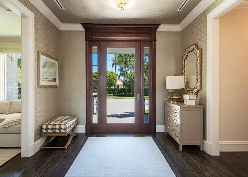 This simple and elegant foyer has a Tropical-style influence to it. It has a glass main door that showcases the beautiful tall tropical trees outside. This matches with the colorful painting of a seaside scenery mounted above the cushioned bench across from the wooden drawers.