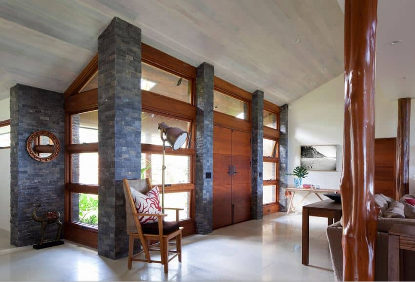 This foyer has a wooden shed ceiling that complements the white walls and the white flooring. These are all contrasted by the dark gray stone pillars that support the redwood double doors as well as its large side lights that are dominated by glass panels.