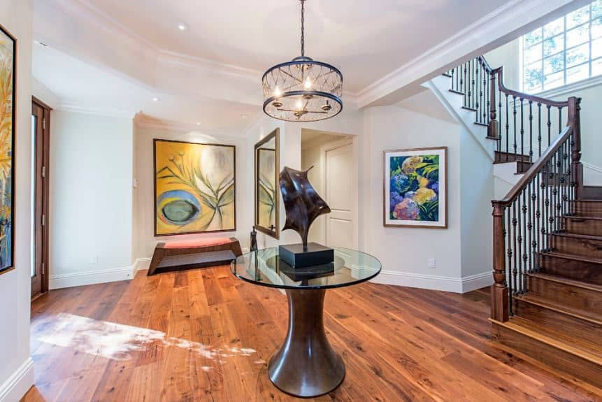This is a spacious Tropical-style foyer with glass doors leading to hardwood flooring with a round glass-top table in the middle bearing an amoeba-like sculpture. This is surrounded by white walls that are adorned with colorful paintings that depicts underwater coral reefs.