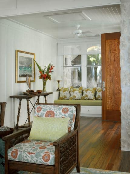 The wooden door of this Tropical-style foyer is filled carvings of tropical trees. This pairs well with the green floral pillows on the built-in bench as well as with the colorful framed photo of a beach scenery mounted above the console table with a tropical plant in a vase.