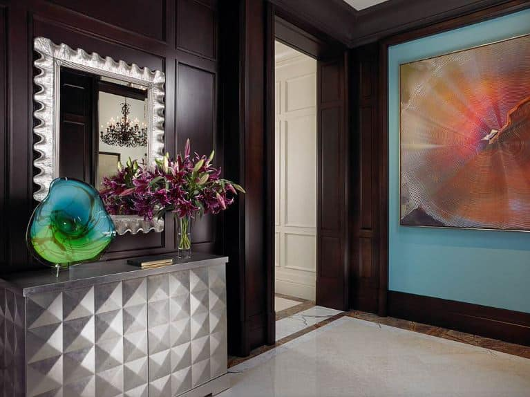 This foyer is a wonderful marriage between Tropical-style and contemporary elements. This foyer has dark wooden walls with an elegant finish. This is adorned with a patterned silver console table with a built-in cabinet that is topped with a matching mirror with a silver frame that looks like a clam shell.