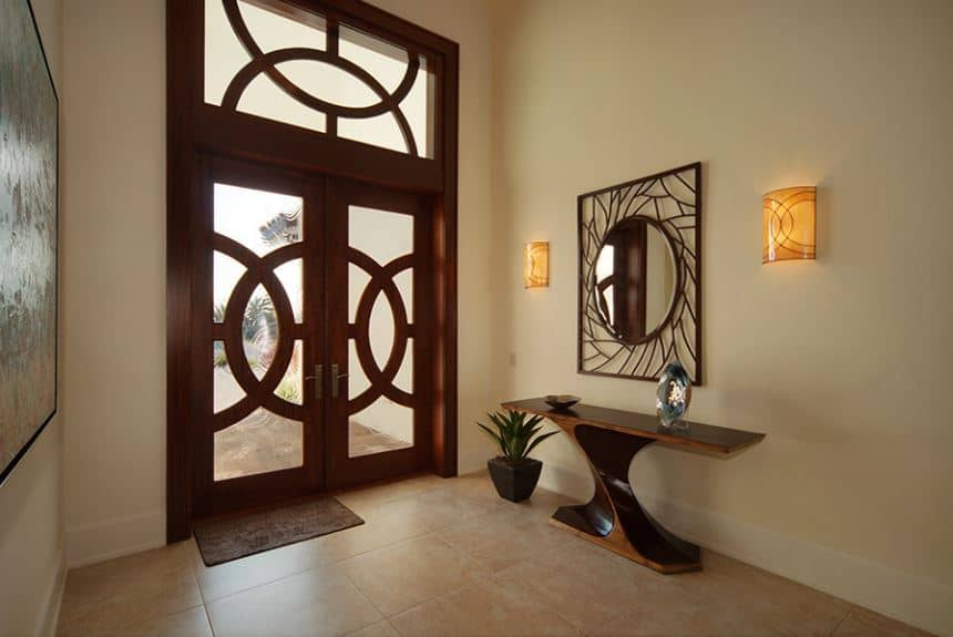 The design of the wooden frames of the double glass doors matches with the large transom window that bring in natural lights to this simple Tropical-style foyer with a wooden console table on the side. This adorned with a potted plant on the side and a decorative mirror above.