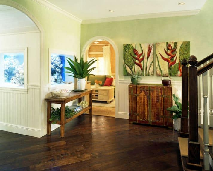 The hardwood flooring of this Tropical-style foyer matches with the wooden console table and the small cabinet adjacent to it. Both of these are adorned with various potted plants and wall-mounted artworks that depicts tropical flowers and plants.
