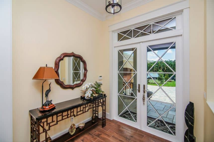 The transom window of this foyer has the same design on its frame as the double doors that are are dominated by glass panels that showcase the beautiful tropical landscape outside. The wooden console table stands out against the beige wall and it is adorned with tropical flowers on top.
