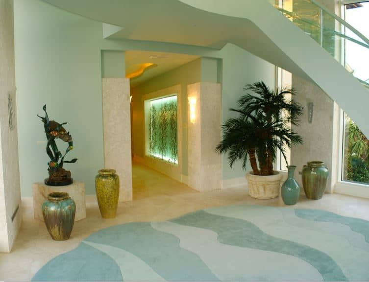 This is a simple Tropical-style foyer with sea green walls that match the charming mural on the floor that depicts the waves of the ocean. This is adorned with various decorative vases, a sculpture that looks like seaweed and a potted tropical plant.
