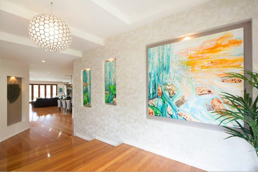 The hardwood flooring that leads to a set of steps down to the rest of the house is contrasted by the white walls that are accented with colorful paintings on its windows that results in a row of unique and colorful glowing paintings that depicts a tropical scene.