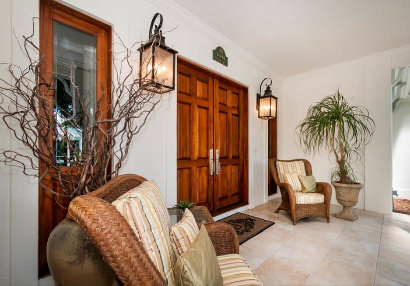 This beautiful Tropical-style foyer has a pair wooden doors flanked with wall-mounted lamps and a couple of woven wicker armchairs paired with decorative jars with tropical plants that stands out against the white walls and white ceiling.