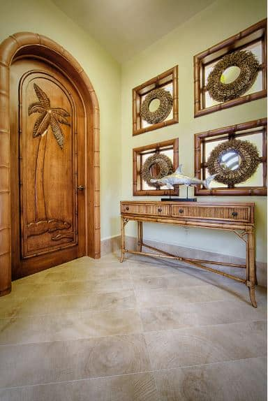 The wooden arched main door of this foyer has a large depiction of a tropical tree on it that matches the over-all aesthetic of the Tropical-style foyer with a set of wooden decorative mirrors above the bamboo console table that stands out against the light gray flooring.