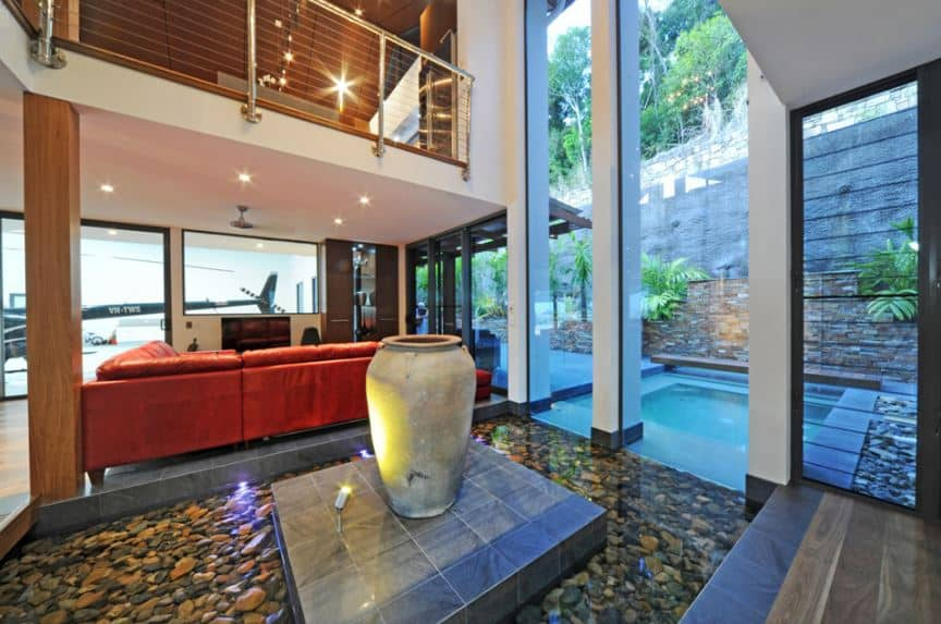 Upon entry of this Tropical-style foyer, You will be welcomed by tall ceilings and a beautiful pond on the side that is filled with clear water emphasizing the decorative river pebbles. In the middle of this is a raised platform with a decorative jar in the middle.