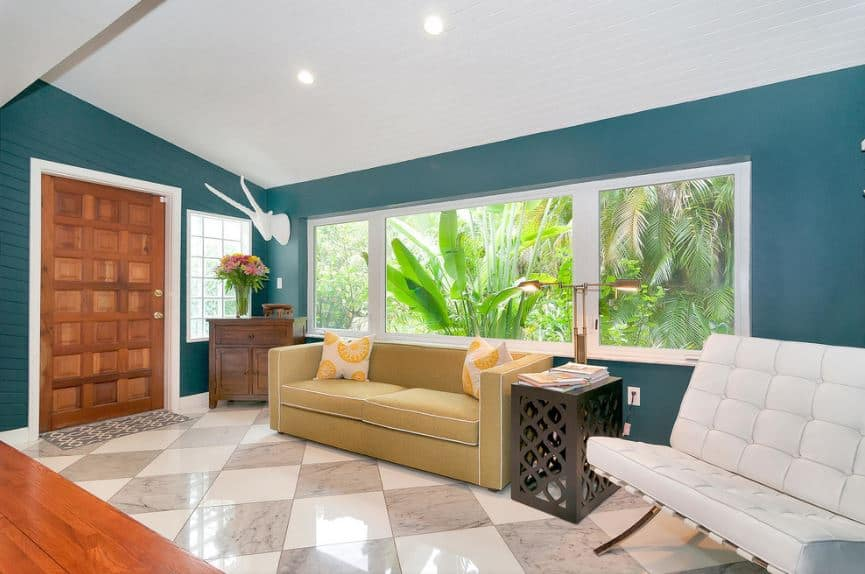 The wonderful green walls of this tropical-style foyer matches the lush green tropical plants just outside the glass window above the comfortable beige couch that stands out against the white and gray checkered flooring and the redwood main door.
