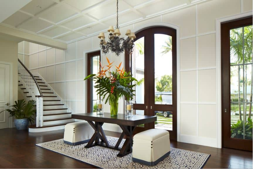Tropical style foyer with coffered ceiling and walls, and a chandelier over a foyer table with seats on an area rug above hardwood flooring.