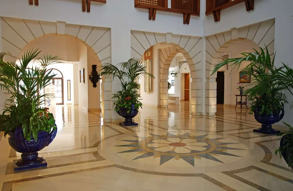 This is a spacious and luxurious Tropical-style foyer with a sleek beige flooring that has a beautiful central floral design surrounded by large dark blue vases bearing tropical plants and flowering shrubs. These stand out against the white walls fitted with beige entry arches.