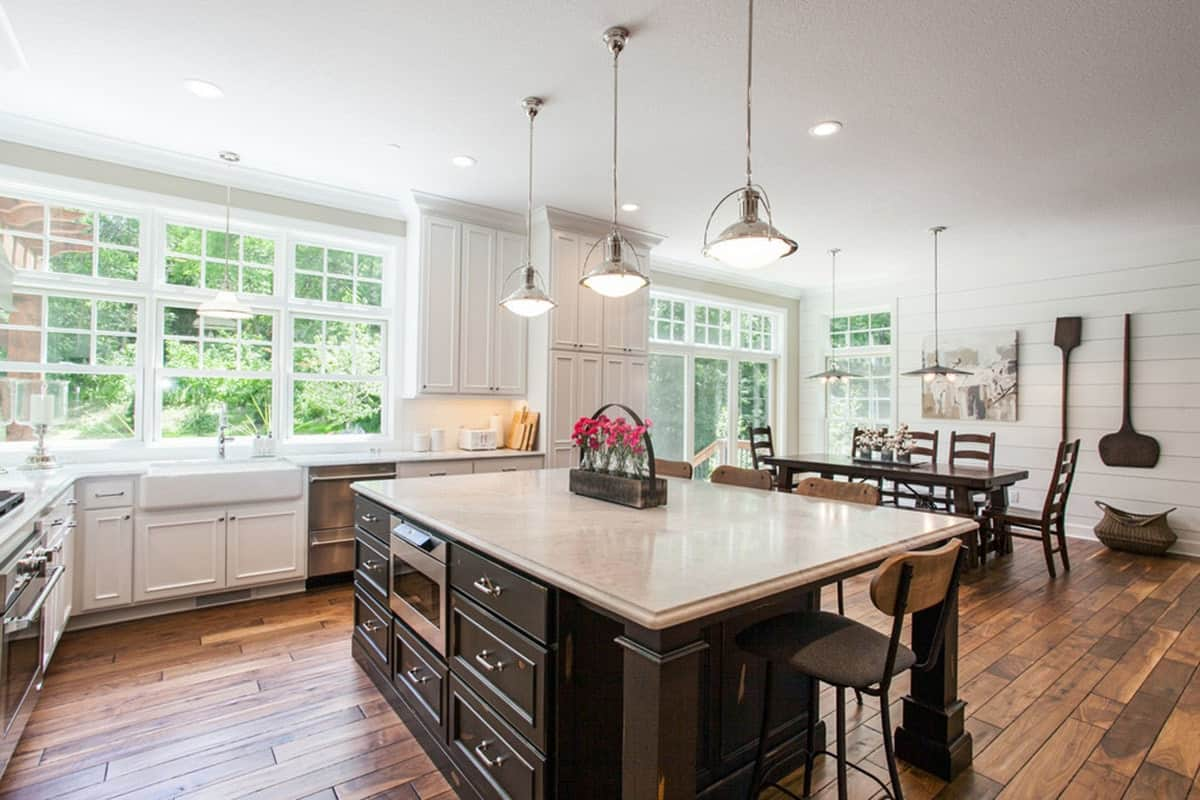 The charming kitchen has a hardwood flooring that goes well with the dark wooden cabinetry of the large kitchen island. This also doubles as the breakfast bar with wrought iron stools topped with simple pendant lights. The high light of this kitchen is the surrounding windows.