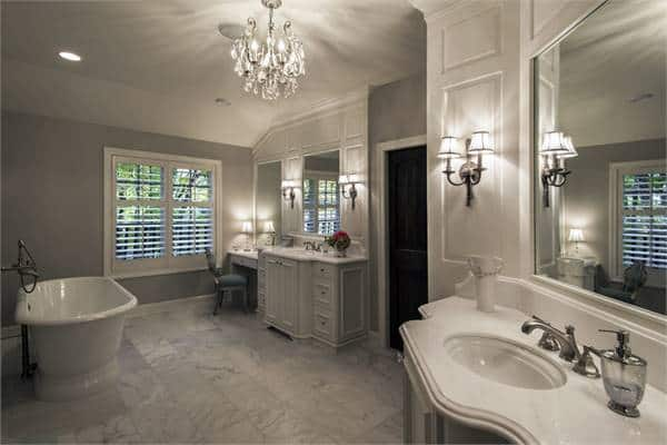 This is a warm and spacious bathroom with a couple of vanities flanking the door. These two vanities are adorned with ornate wall lamps that match with the large chandelier hanging in the middle by the freestanding bathtub across from the vanities.