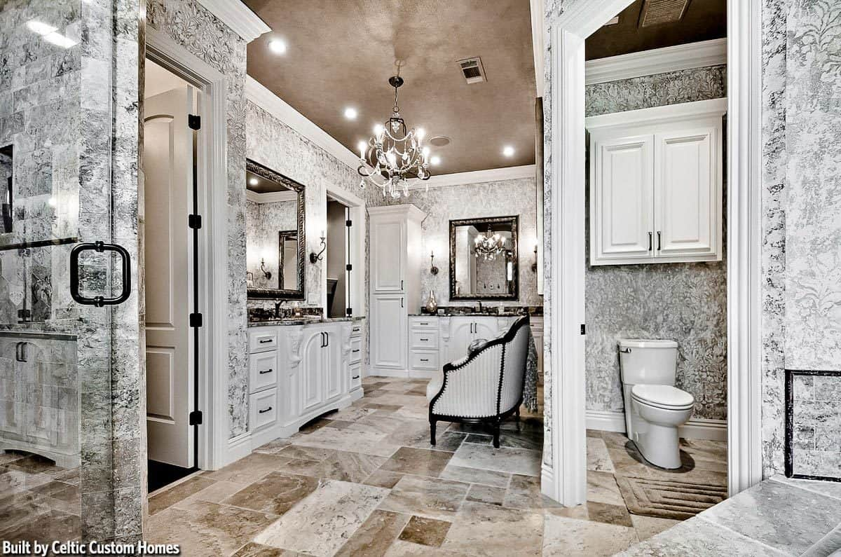 The gray marble flooring of this primary bathroom is complemented by the wallpaper and the gray ceiling that hangs a chandelier over the vanity area that has two sinks and white cabinetry.