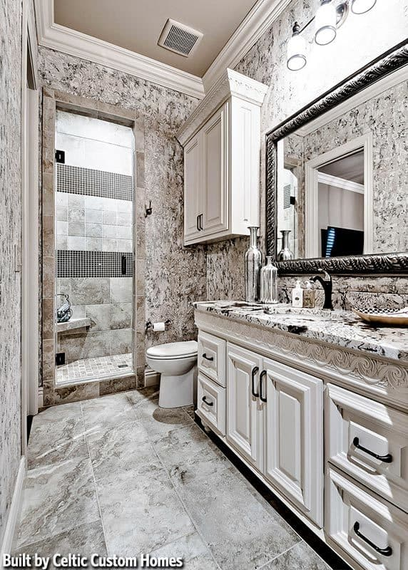 This simple yet lovely bathroom has the same gray patterns to its marble floor, walls and the countertop of the vanity beside the toilet. On the other side of this toilet is the glass door of the walk-in shower area.