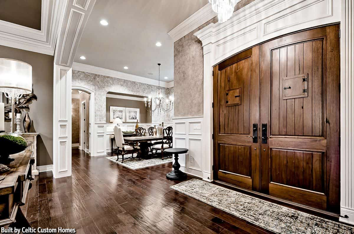 The charming foyer has a wooden front double door, a cascading crystal chandelier, and a vintage runner flanked by black round tables that stand out against the white wainscoting of the walls.