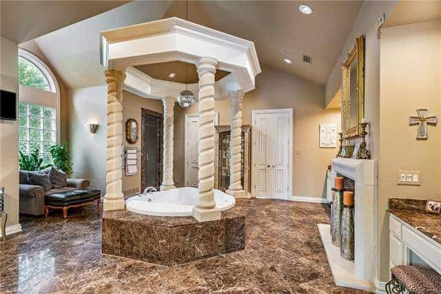 This primary bathroom has lovely granite-top vanities, a fireplace, gray couch, and an elegant deep soaking tub surrounded by spiral columns and inlaid with the same earthy marble as the floor.