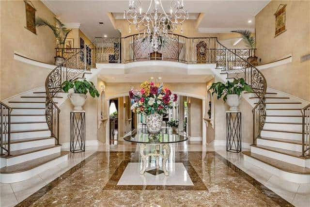 The grand foyer has a gorgeous marble flooring paired with a round glass-top center table, intricate chandelier, and flower pedestals sitting against the elegant bifurcated staircase.