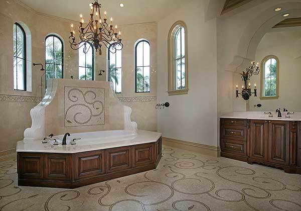 This is a spacious and grand primary bathroom with a large bathtub in the center of the beige floor adorned with swirls and topped with a tall ceiling that hangs a large wrought iron chandelier.