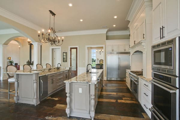 This is a gorgeous kitchen with enough space for two kitchen islands with a gray tone to contrast the dark hardwood flooring. These are then surrounded by beige walls and a beige ceiling that hangs a wrought-iron chandelier over the breakfast bar.