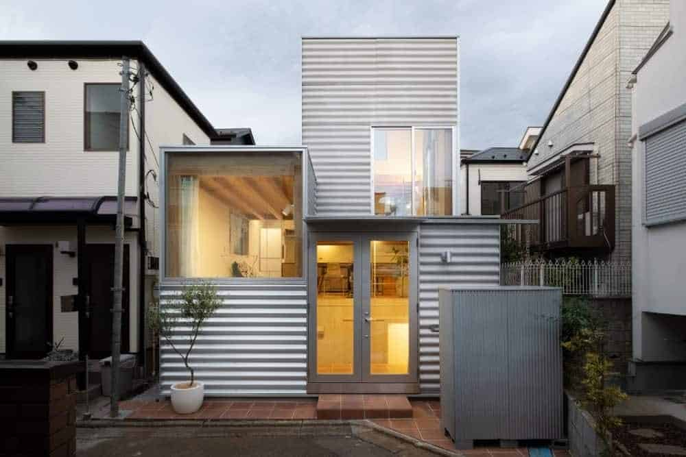 This is a front view of the small house with corrugated tin exterior walls complemented by the large glass walls complemeted by the warm lighting of the interiors and the potted plant,