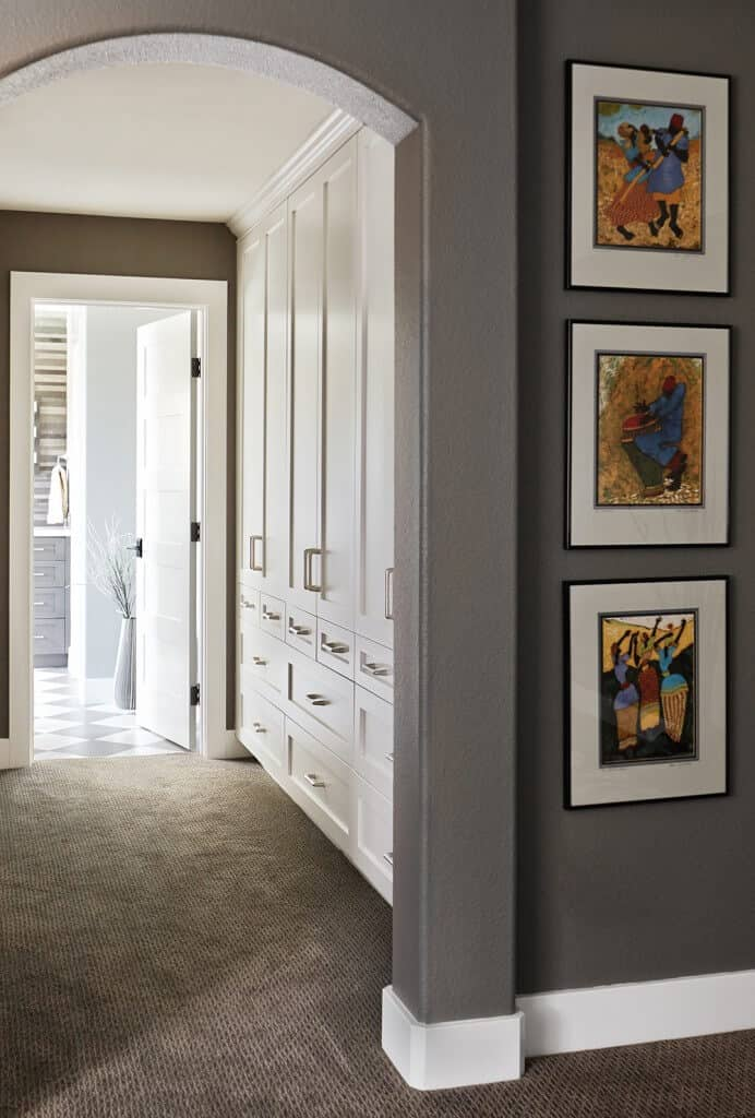 Colorful artworks accentuate the gray archway that leads to this walk-in closet with white wardrobe cabinets over carpet flooring.