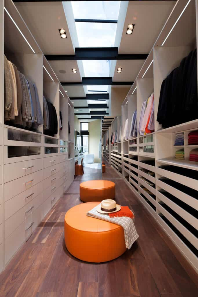 Orange leather seats bring a pop of color in this long and narrow walk-in closet showcasing wide plank flooring and a regular white ceiling fitted with recessed lights and a skylight that runs the length of the room.