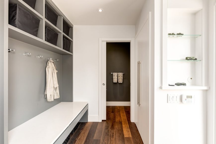 This walk-in closet offers a white wardrobe and an inset wall niche fitted with glass shelves. It includes a built-in seat that's fixed under chrome coat racks and open shelving filled with black storage bins.