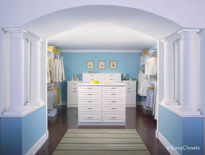 Charming walk-in closet with blue walls and an open archway lined with white columns. It is decorated with black framed artworks and a striped area rug that lays on the dark hardwood flooring.