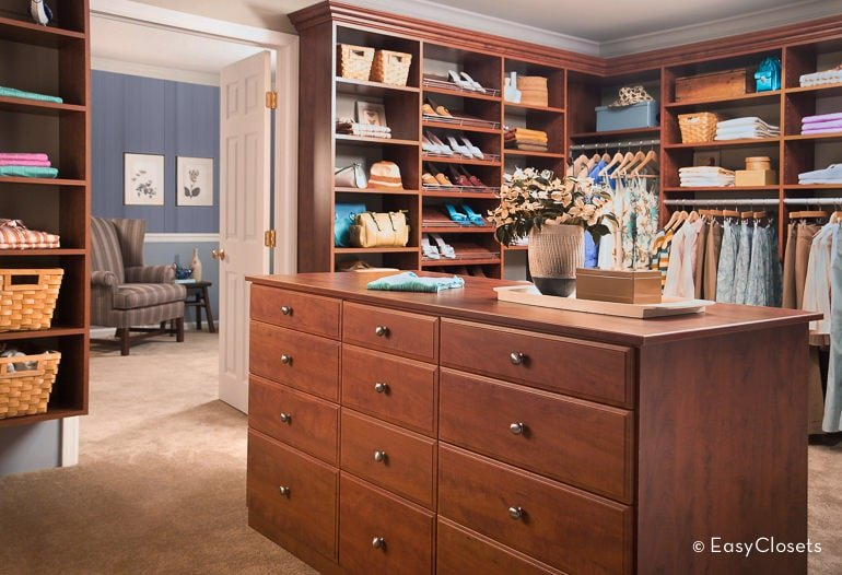 A white door accented with brass hardware opens to this walk-in closet with open shelving and a natural wood island fitted with ample drawers for additional storage.