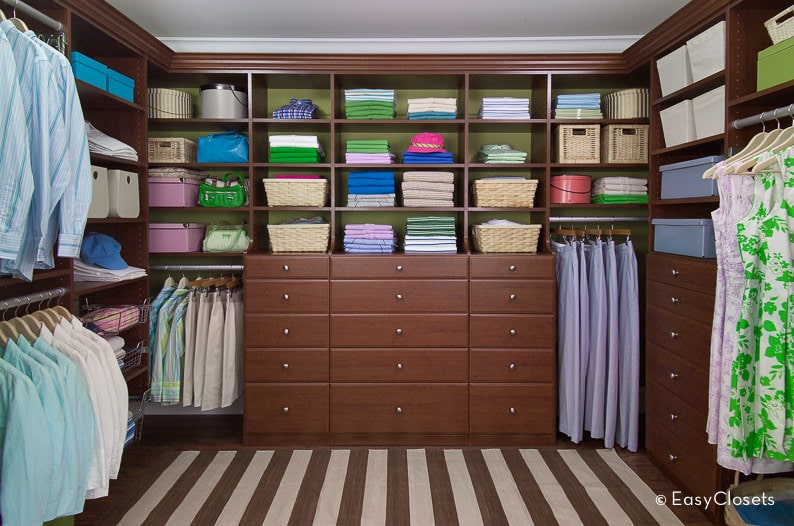 A brown striped rug adds a striking accent in this walk-in closet with open shelving and wooden drawers fitted with stainless steel knobs.