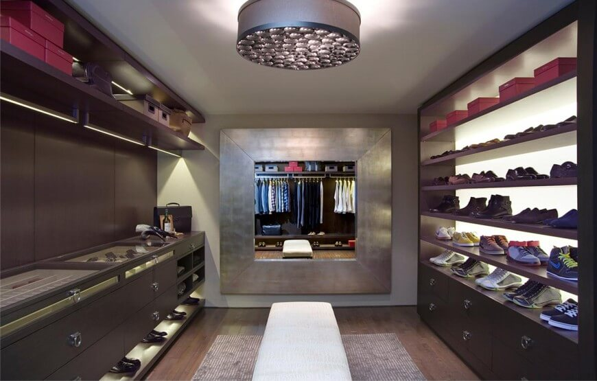 Trendy walk-in closet decorated with a stylish drum chandelier and a large framed mirror mounted on the taupe wall. It boasts dark wood storage with a beige cushioned bench in the middle that sits on a striped rug over the hardwood flooring.
