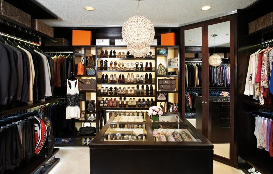 Sophisticated walk-in closet with mirrored wardrobe doors and open storage surrounding a glass top island that's illuminated by fancy round crystal chandeliers.