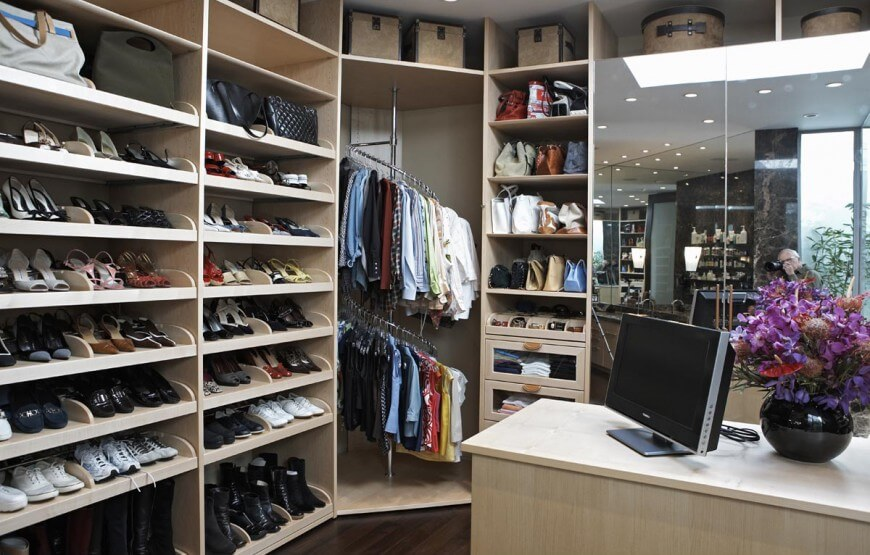 This walk-in closet features mirrored wardrobe doors and spiral clothing racks flanked by open shelving. There's a light wood island in the middle that's topped with a display screen and a black flower vase.