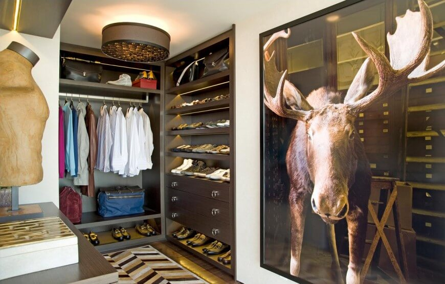 A large stag artwork brings character in this walk-in closet with dark wood storage and a striking herringbone rug over hardwood flooring illuminated by a drum flush mount light.