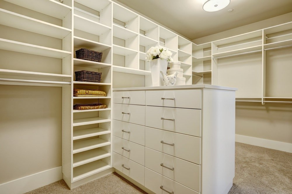 Simple walk-in closet showcases open shelving and a white dresser that's topped with round storage boxes and a sleek vase. It has gray carpet flooring and a regular ceiling mounted with a flush light.