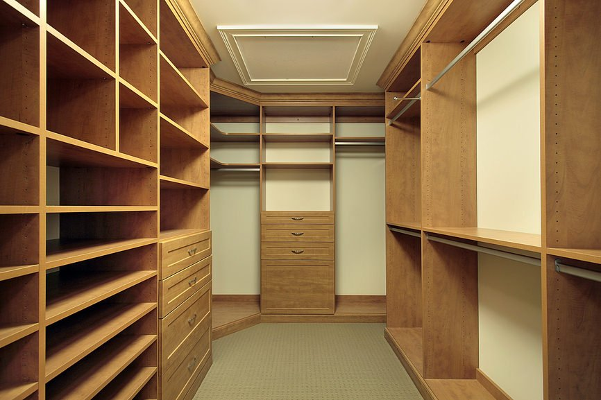 Natural wood cabinets run throughout this walk-in closet with taupe carpet flooring and beige walls matching with the regular ceiling.