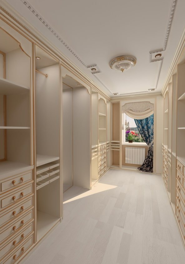 Long and narrow walk-in closet with an elegant flush mount light and white cabinets accented with gold trims and pulls. There's a picture window at the far end that's dressed in a blue floral drapery.