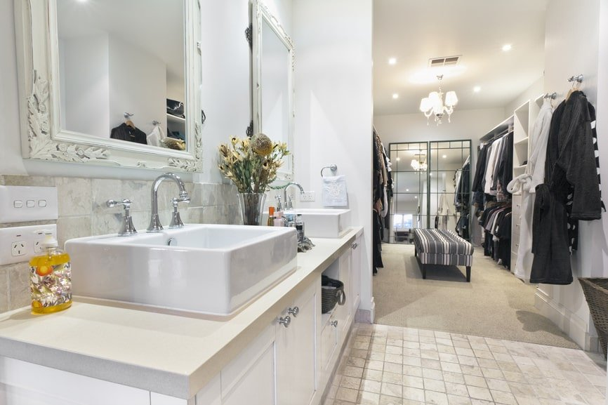 A walk-in closet inside the primary bathroom offering ample storage and a striped bench in the middle that sits on gray carpet flooring. It is illuminated by a gorgeous chandelier and recessed ceiling lights.